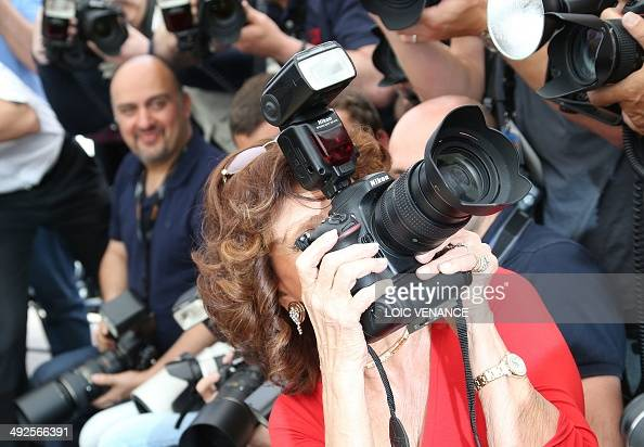 Italian actress Sophia Loren holds a professional camera ...