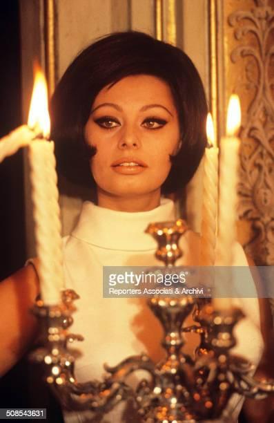 Italian actress Sophia Loren in a posed portrait behind a chandelier 1960s