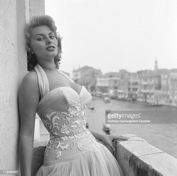 Italian actress Sophia Loren leaning on a wall portayed on a terrace on the Canal Grande wearing a white embroidered dress Venice 1955