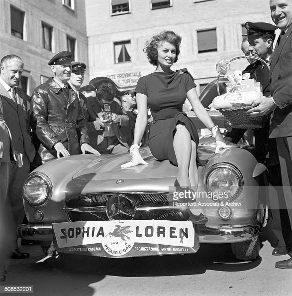 Italian actress Sophia Loren on the hood of a car at the Rally of Cinema III Rome 1956
