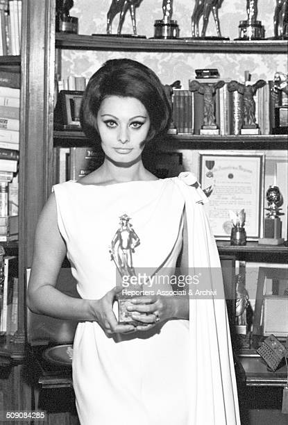 Italian actress Sophia Loren posing in her home with David di Donatello award for 'Yesterday Today and Tomorrow' 1964