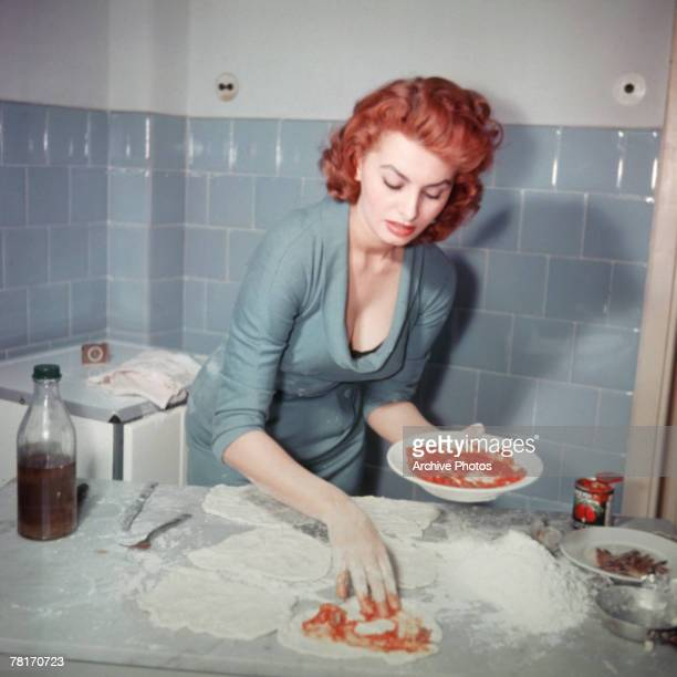 Italian actress Sophia Loren prepares an Italian dish circa 1965