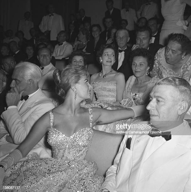 Italian actress Sophia Loren sitting among the audience at the Venice Movie festival talking to Elsa Maxwell Lido Venice 1958