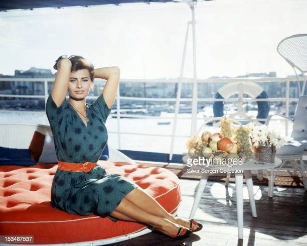 Italian actress Sophia Loren sitting at the side of a harbour circa 1960