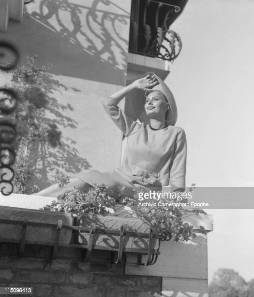 Italian actress Sophia Loren sitting on a terrace floor smoking a cigarette wearing a tailleur a beads necklace and a widebrimmed hat flower pots...