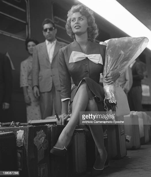 Italian actress Sophia Loren sitting on her suitcases on the track at the railway station Venice 1955