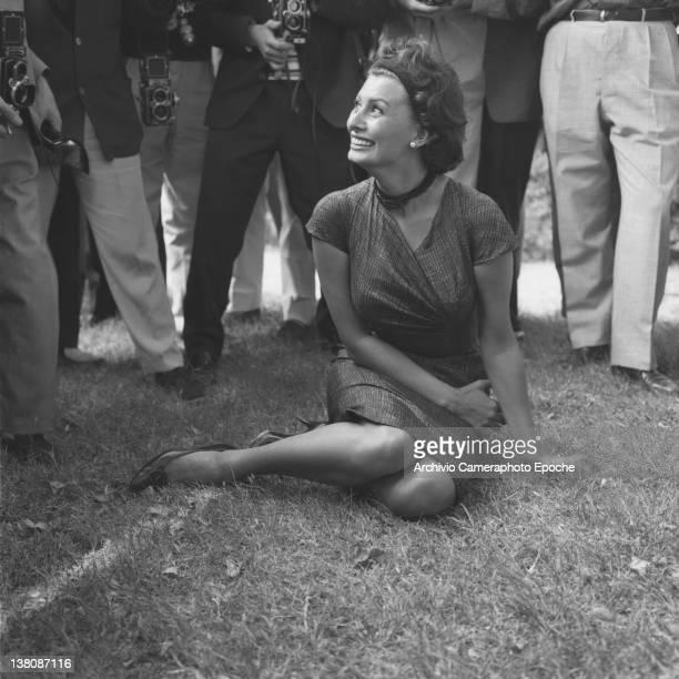Italian actress Sophia Loren sitting on the grass among photographers Lido Venice 1958