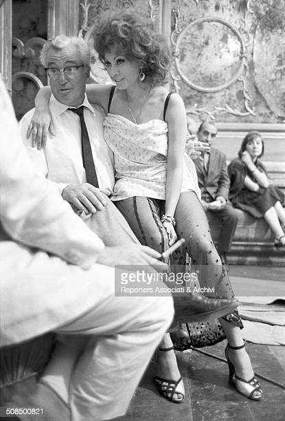 Italian actress Sophia Loren sitting on the lap of Italian director Vittorio De Sica during a break on the set of the film 'Marriage Italian Style'...