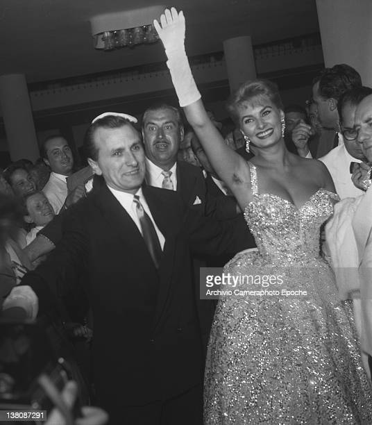 Italian actress Sophia Loren waving at the Movie Festival wearing an evening dress and long white gloves Lido Venice 1955