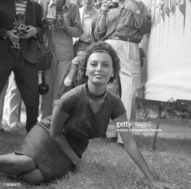 Italian actress Sophia Loren wearing a fancy dress a headband a beads necklace and pearl earrings sitting on the grass posing for photographers...