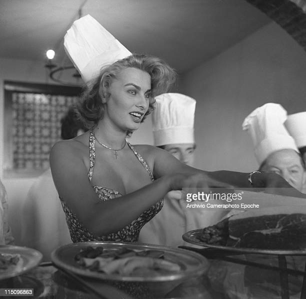 Italian actress Sophia Loren wearing a floral dress a chef's hat and a crucifix necklace cutting slices of ham with a big knife surrounded by cooks...