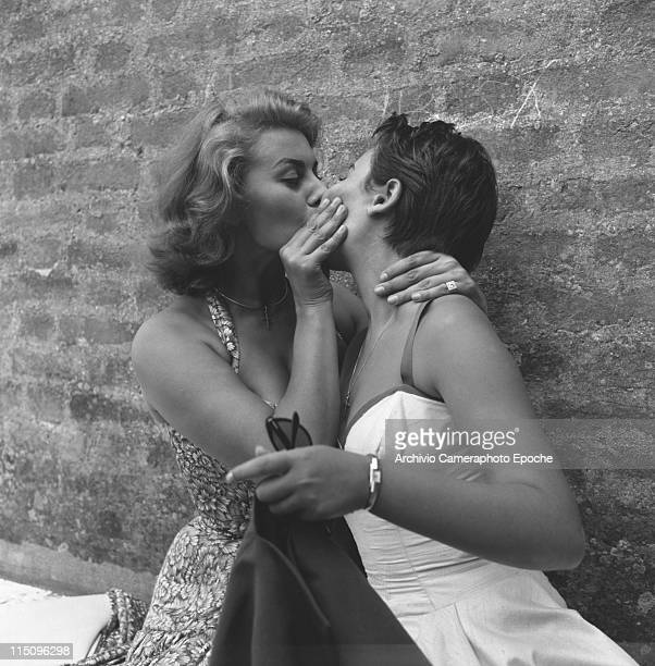 Italian actress Sophia Loren wearing a floral dress kissing on the lips her sister Maria Scicolone holding sunglasses and a blazer Venezia 1955