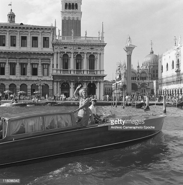Italian actress Sophia Loren wearing a tailleur and a widebrimmed hat greeting from a water taxi in front of St Mark Square the taxi driver looking...
