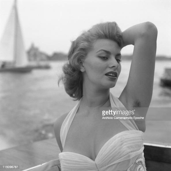 Italian actress Sophia Loren wearing a white embroidered dress posing for the photographer a sail on the sea in the background Venice 1955