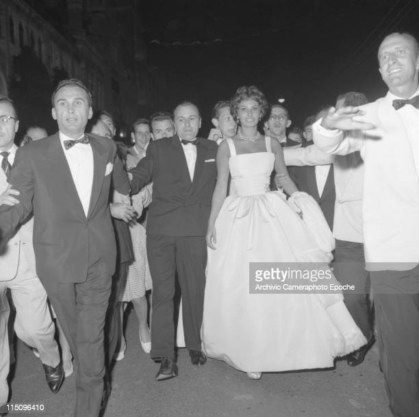 Italian actress Sophia Loren wearing a white evening dress and and jewels earrings and necklace surrounded by bodyguards wearing suits a crowd behind...