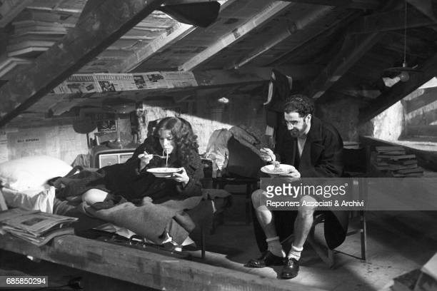 Italian actress Stefania Sandrelli sitting on a cot and Italian actor Stefano Satta Flores sitting on a chair both eating spaghetti Scene set in an...