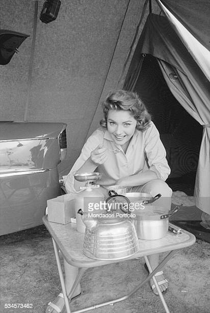 Italian actress Sylva Koscina eating food prepared with a camping fire during the XVIII Venice International Film Festival Venice 1957