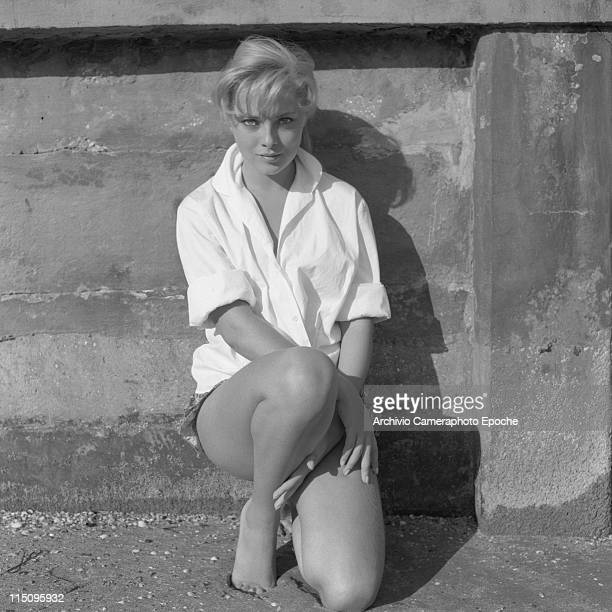 Italian actress Virna Lisi wearing a white shirt and hotpants standing on her knees leaning against the wall on the beach Lido Venice 1958