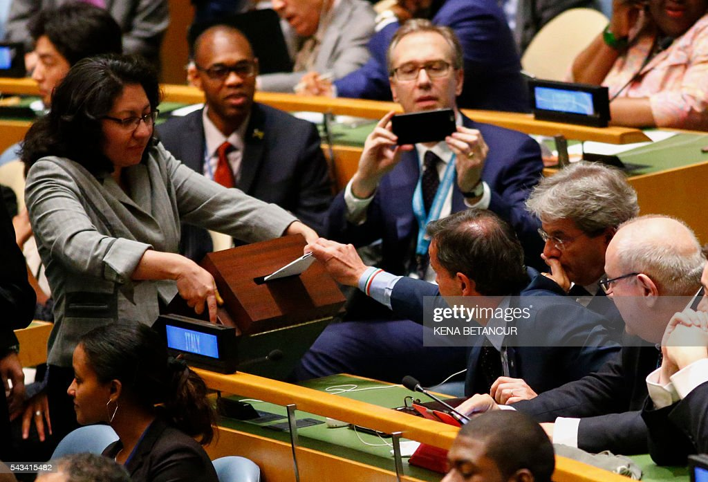 Italian Ambassador to the UN Sebastiano Cardi casts his vote, next to Italian Foreign Minister Paolo Gentiloni (L) during election of five non-permanent members of the Security Council at the General Assembly Hall at the United Nations in New York on June 28 2016. Three European countries and two Asian nations are battling for seats on the UN Security Council in elections that are drawing attention to the refugee crisis and human rights. / AFP / KENA