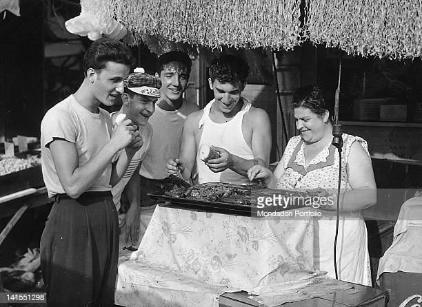 Italian American boys watching a woman cooking meat on a grill at a stall of Little Italy market New York 1950s