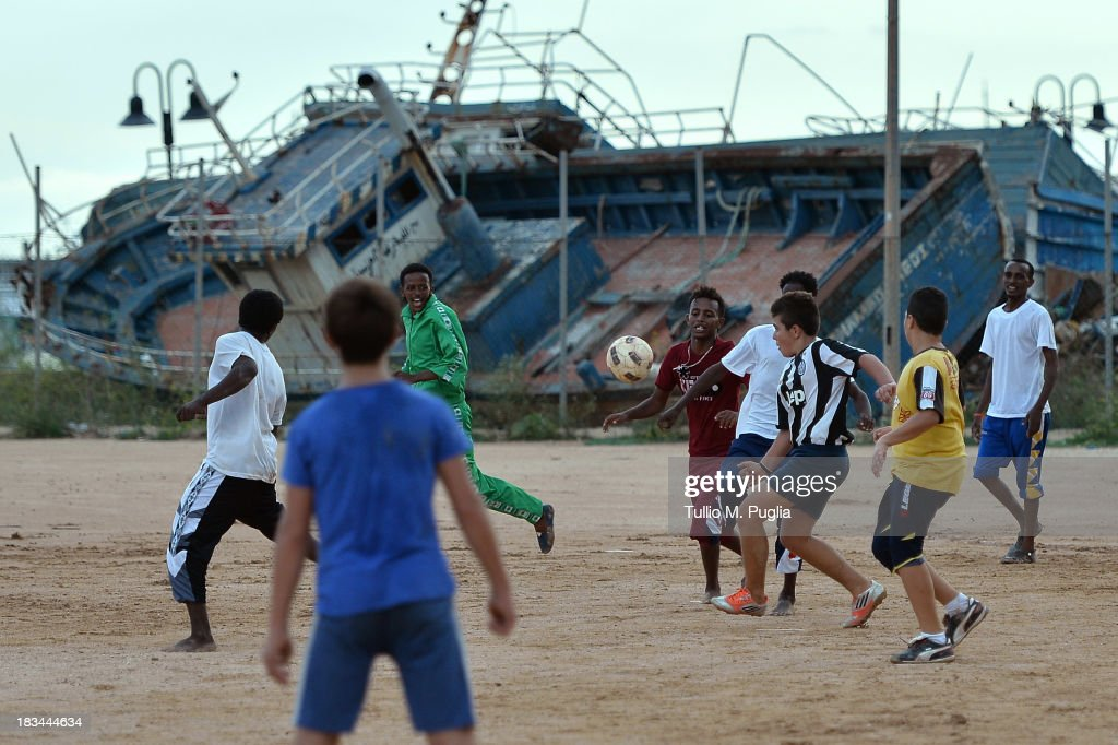 Italian and Eritrean migrant boys play football at Lampedusa Football Field where boats fomerly used by immigrants arriving in Lampedusa lie disused on October 6, 2013 in Lampedusa, Italy. The search for bodies continues off the coast of Southern Italy as the death toll of African migrants who drowned as they tried to reach the island of Lampedusa is expected to reach over 300 people. The tragedy has bought fresh questions over the thousands of asylum seekers that arrive into Europe by boat each year.