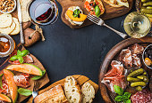 Italian antipasti wine snacks set. Brushettas, cheese variety, Mediterranean olives, pickles, Prosciutto di Parma with melon, salami and wine in glasses over black grunge background, top view, copy sp