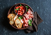 Italian antipasto - tomatoes bruschetta and prosciutto. On a dark background, top view. Delicious snack or appetizer for wine