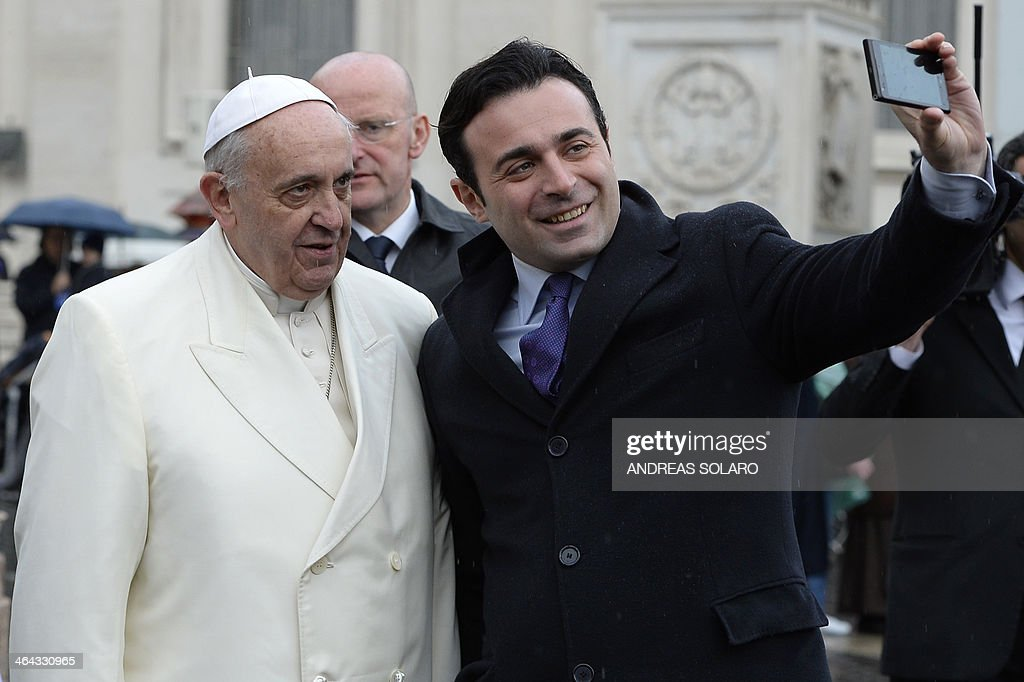 Italian Antonio Di Lucia takes a 'selfie' with Pope Francis at the end of a general audience at St Peter's square on January 22 2014 at the Vatican...