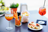Italian aperitives/aperitif: two glasses of cocktail (sparkling wine with Aperol and Bellini cocktail) and appetizer platter on the table