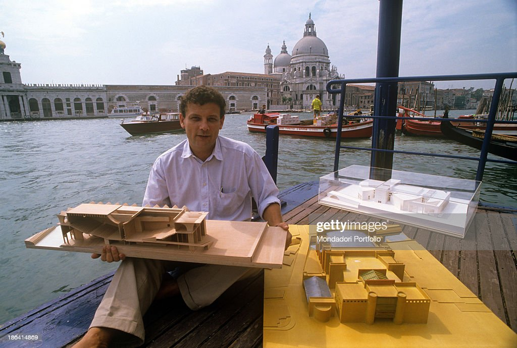 Italian architect Francesco Dal Co sitting on the Grand Canal bank and  showing the model of