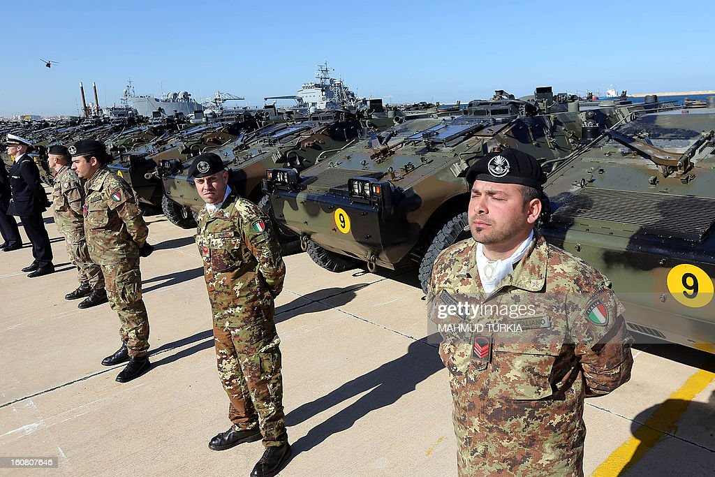 Italian Army soldiers stand by some of the twenty military vehicles during an handing over ceremony by Italy to Libya at a Libyan Navy Base on February 6, 2013 in Tripoli.