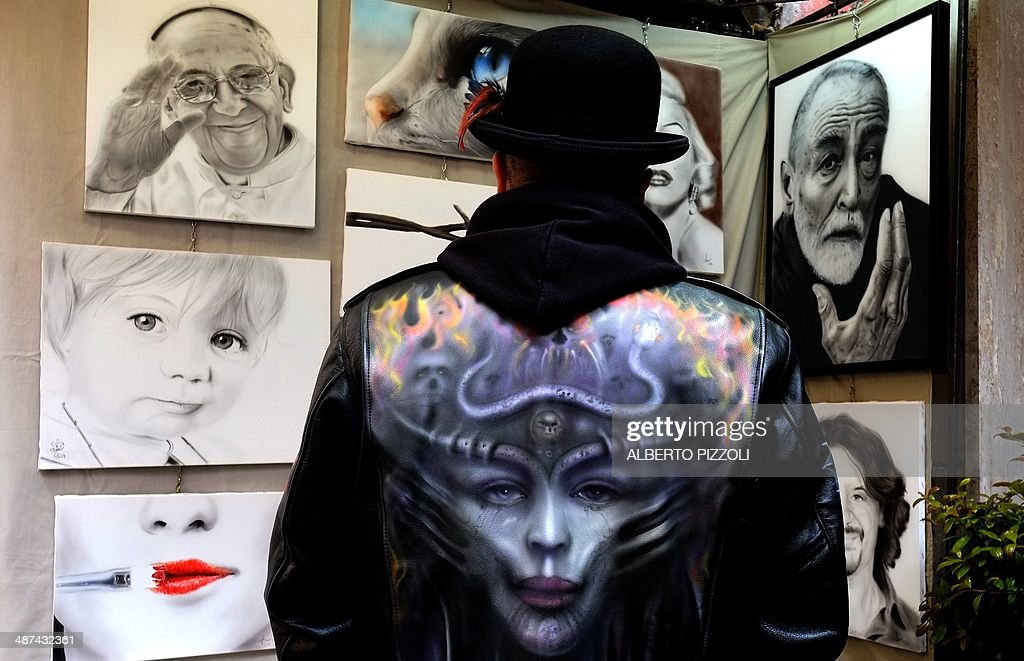 CAPTION === Italian artist 'Frans' looks at his work in the Via Margutta during the annual exhibition 100 Painters on Via Margutta on April 30, 2014 in Rome. The One hundred painters exhibition was first held in the 1950s in the Via Margutta, a small Roman street renowned for inspiring the works of sculptors, painters, poets and film directors. In the early 1950s, Audrey Hepburn and Gregory Peck made a film called Roman Holiday and the Via Margutta, which features in the film, became the haunt of artists such as Frederico Fellini and is now an exclusive residential street.