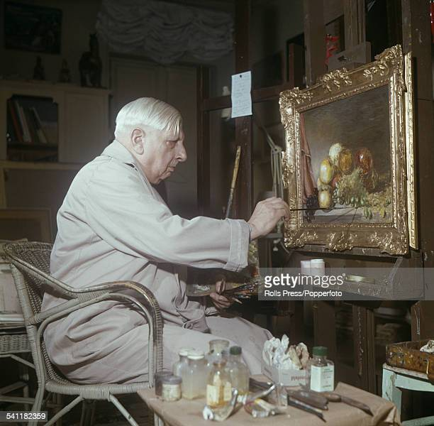 Italian artist Giorgio de Chirico pictured putting finishing touches to an oil painting in his studio in Rome Italy circa 1962