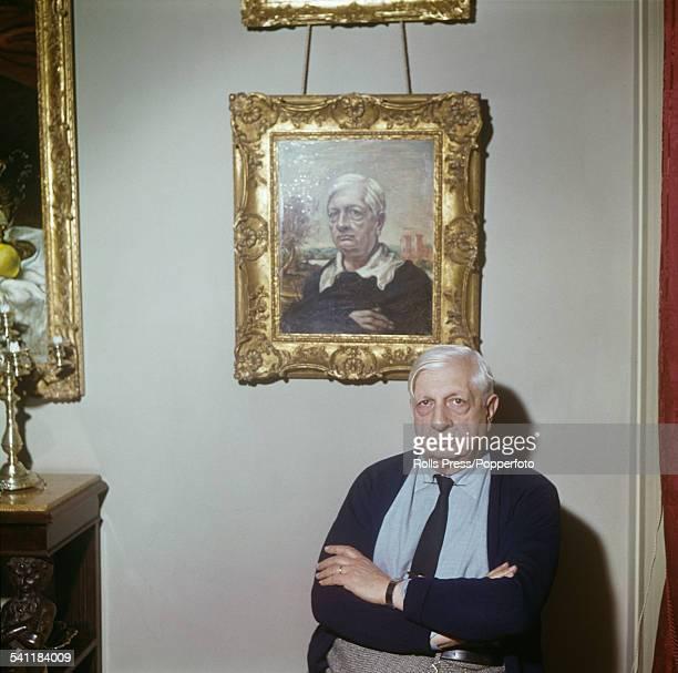Italian artist Giorgio de Chirico pictured sitting below a self portrait painting in his studio in Rome Italy circa 1962