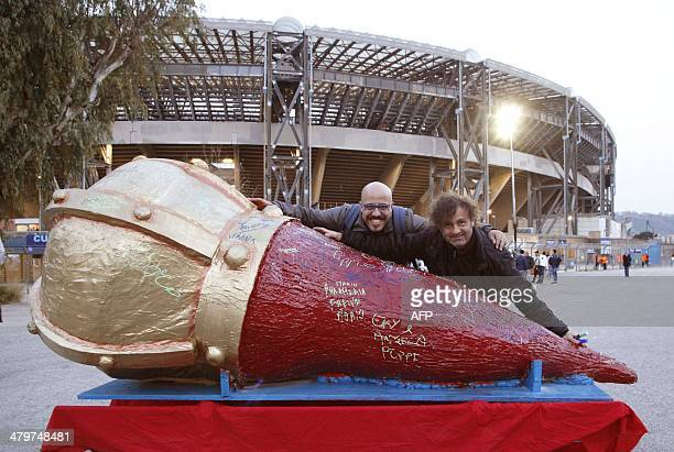 Italian artists Pippo Lacapruccia and Francesco Amato pose behind their sculpture a giant horn which is a traditional Napolitan talisman before the...