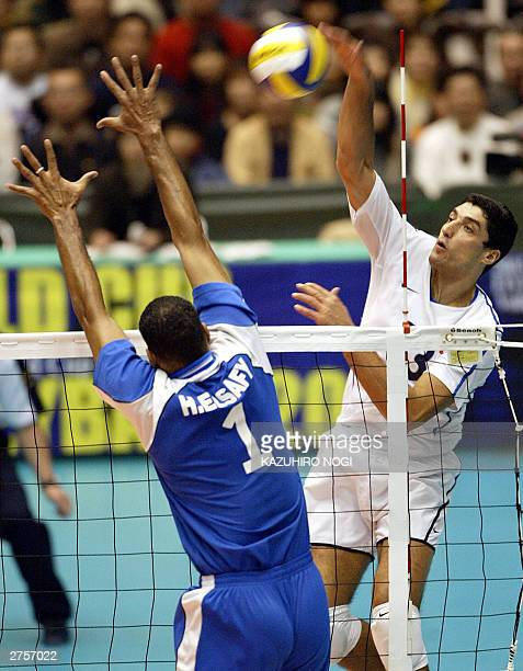 Italian attacker Andrea Giani spikes the ball past Egyptian defender Hamdy Awad during the World Cup men's volleyball tournament at the Okayama...