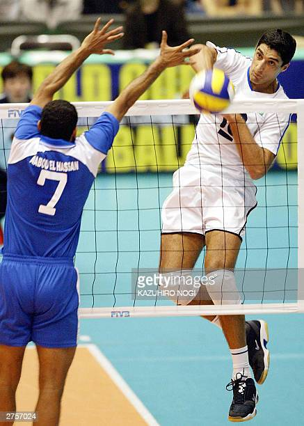 Italian attacker Andrea Giani spikes the ball past Egyptian defender Ashraf Abouel Hassan during the World Cup men's volleyball tournament at the...