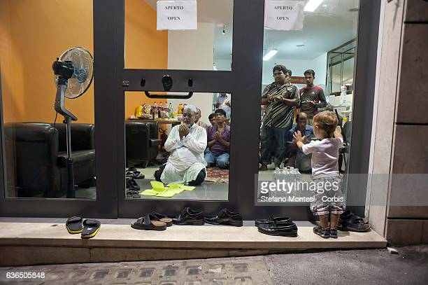 Italian baby look intrigued men praying inside a shop of migrants from Bangladesh before the Iftar the meal that breaks the fast during the month of...