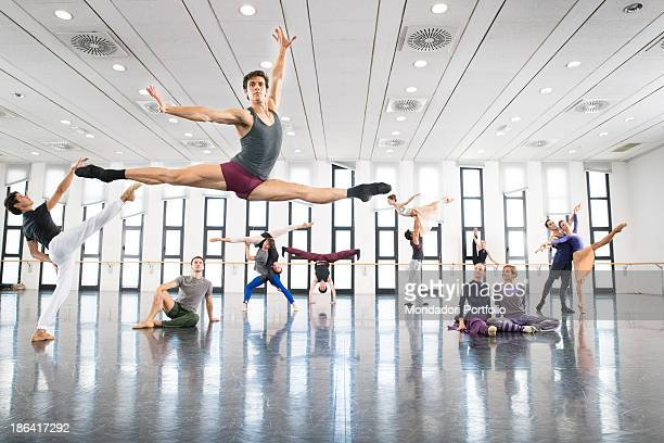 Italian ballet dancer Roberto Bolle performing a grand jeté at the dance studio Behind him some dancers of La Scala Theatre ballet company Massimo...