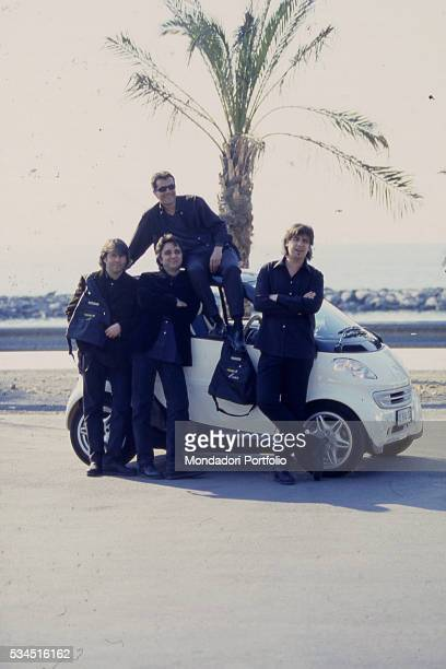 Italian band 'Stadio' posing on the seafront leaning against a Smart car From the left the guitarist Andrea Fornili the singer and keyboard player...