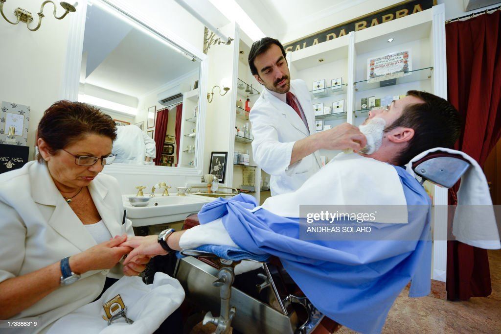 Italian barber Alessandro Migliacci (C, back) shaves a customer in his barber shop 'Antica Barbieria Peppino 1956' in central Rome on July 12, 2013, as his assistant gives the customer a manicure. The well-known barber shop is frequented by lawyers, politicians, deputies, senators and famous journalists.