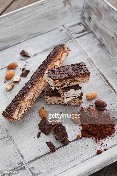 Italian bars of nougat, almond, hazelnut, cocoa powder, chocolate on wooden tray