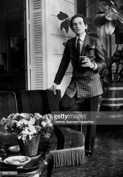 Designer Pierre Cardin wearing a spotted evening jacket while resting one leg on the arm of the couch with a drink