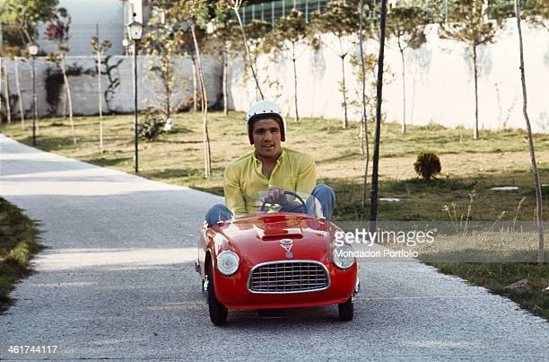 Italian boxer Nino Benvenuti drives through the boulevard of the garden of his villa onboard the red car of one of his sons wearing a helmet the...