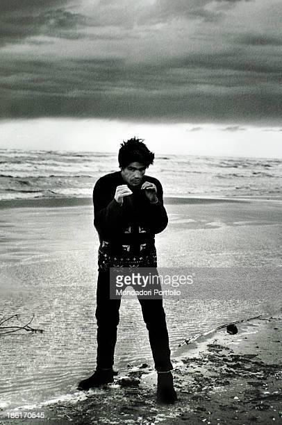 Italian boxer Nino Benvenuti posing on a beach keeping his fists close to his chest Rimini 1960s