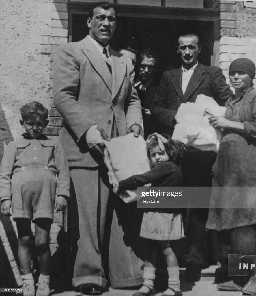 Italian boxer Primo Carnera handing a little girl a blanket as he helps to distribute American Red Cross supplies following the war Italy May 14th...