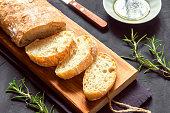 Italian bread Ciabatta and rosemary on black background - fresh homemade bread bakery