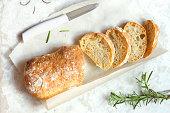 Italian bread Ciabatta and rosemary on white marble background - fresh homemade bread bakery