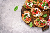 Italian bruschetta with tomatoes,feta and basil pesto on a cutting board on a. grey concrete or stone background.Top view.