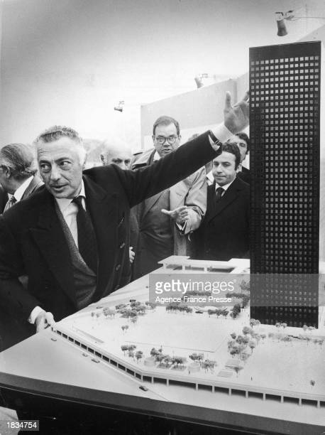 Italian businessman Gianni Agnelli the president of Fiat company points to a model of the company's new highrise office building to be built in La...